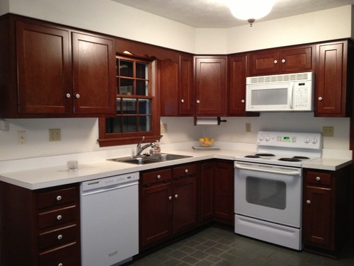 Brown cabinets white corian countertop w white appliances for Cherry kitchen cabinets with white appliances