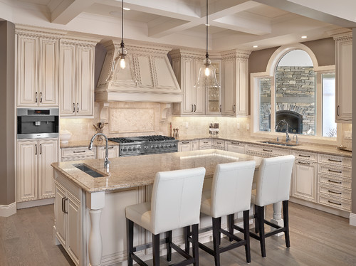 Cambria Berkeley Countertop and Overhang Island Top with English Cream Paint Maple Cabinets, Travertine Backsplash and Travertine Herringbone Set up Inlay, Porcelain Flooring and Transparent Kitchen Pendants