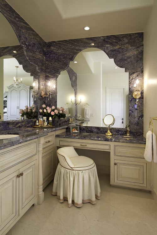 This ultra-feminine bathroom features mirrors embedded in an extension of the purple and cream granite that forms the countertops.