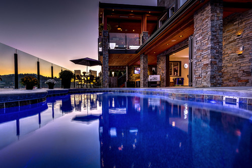 Dark blue pool beside a contemporary lodge