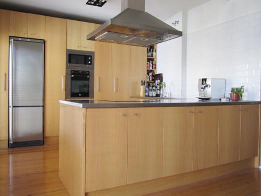 Mobiliario de cocina a medida acabada en madera de haya y acero inoxidable ma...