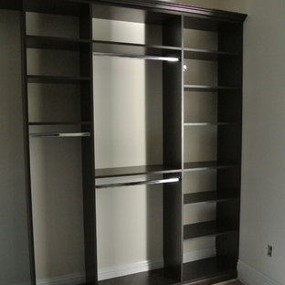 This is an example of a large classic gender neutral walk-in wardrobe in Miami with raised-panel cabinets, dark wood cabinets and travertine flooring.