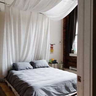 Großes Eklektisches Schlafzimmer im Loft-Style mit weißer Wandfarbe, hellem Holzboden und Ziegelwänden in Montreal