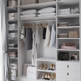 Photo of a small scandinavian gender-neutral walk-in wardrobe in Other with white cabinets, medium hardwood floors, brown floor and open cabinets.