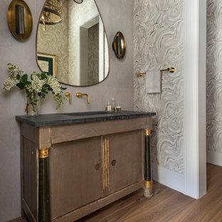 Bild på ett vintage svart svart toalett, med ljust trägolv, ett undermonterad handfat och marmorbänkskiva