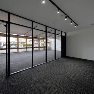 他の地域の巨大なインダストリアルスタイルのおしゃれなアトリエ・スタジオ (白い壁、カーペット敷き、自立型机、黒い床、表し梁、壁紙) の写真