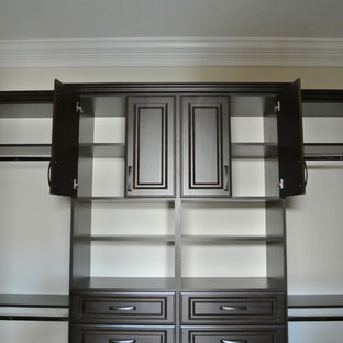 This is an example of a large traditional gender neutral walk-in wardrobe in Miami with raised-panel cabinets, dark wood cabinets and travertine flooring.