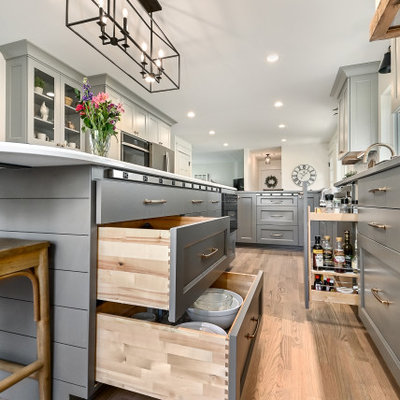 Example of a huge country l-shaped medium tone wood floor and brown floor eat-in kitchen design in Milwaukee with a farmhouse sink, shaker cabinets, gray cabinets, quartz countertops, white backsplash, marble backsplash, stainless steel appliances, an island and gray countertops