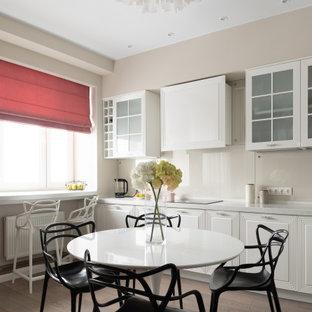 Идея дизайна: прямая кухня-гостиная среднего размера в стиле современная классика с монолитной раковиной, стеклянными фасадами, белыми фасадами, столешницей из акрилового камня, бежевым фартуком, фартуком из стекла, черной техникой, полом из ламината, коричневым полом, серой столешницей и балками на потолке без острова