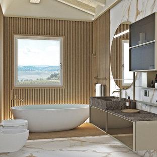 Bild på ett litet funkis brun brunt badrum med dusch, med luckor med glaspanel, beige skåp, ett fristående badkar, en kantlös dusch, en vägghängd toalettstol, vit kakel, porslinskakel, beige väggar, klinkergolv i porslin, ett integrerad handfat, marmorbänkskiva, vitt golv och dusch med gångjärnsdörr
