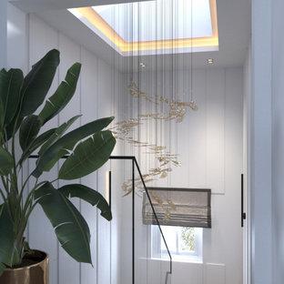 """Immagine di una scala a """"L"""" contemporanea di medie dimensioni con pedata in legno, alzata in legno, parapetto in vetro e pannellatura"""