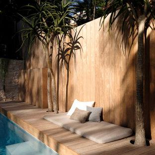Foto di una grande piscina monocorsia contemporanea rettangolare dietro casa con paesaggistica bordo piscina e pedane