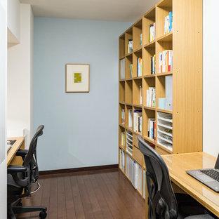 Idéer för mellanstora nordiska hemmabibliotek, med blå väggar, mörkt trägolv och ett fristående skrivbord