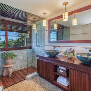 ハワイの広いトロピカルスタイルのおしゃれな浴室 (濃色木目調キャビネット、アルコーブ型シャワー、グレーのタイル、白い壁、ベッセル式洗面器、木製洗面台、グレーの床、オープンシャワー、ブラウンの洗面カウンター、洗面台2つ、造り付け洗面台) の写真