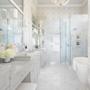 This is an example of a mid-sized traditional master bathroom in Charleston with recessed-panel cabinets, grey cabinets, white tile, porcelain tile, porcelain floors, an undermount sink, engineered quartz benchtops, white floor, a hinged shower door, grey benchtops, an enclosed toilet, a double vanity, a built-in vanity, wallpaper and a freestanding tub.