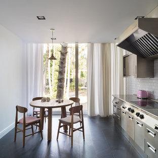 Стильный дизайн: линейная кухня в современном стиле с плоскими фасадами, фасадами из нержавеющей стали, столешницей из нержавеющей стали, белым фартуком, фартуком из плитки кабанчик, черным полом и серой столешницей без острова - последний тренд