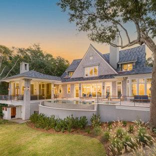 Пример оригинального дизайна: двухэтажный, деревянный, серый частный загородный дом в морском стиле с крышей из гибкой черепицы, синей крышей и отделкой дранкой