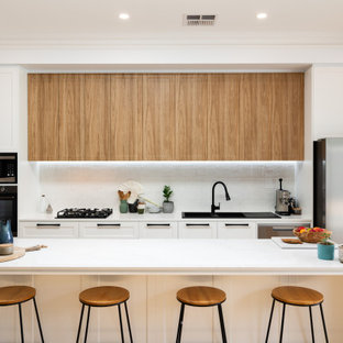 This is an example of a large contemporary kitchen in Adelaide with a double-bowl sink, shaker cabinets, white cabinets, quartz benchtops, white splashback, cement tile splashback, stainless steel appliances, light hardwood floors, with island, brown floor and white benchtop.
