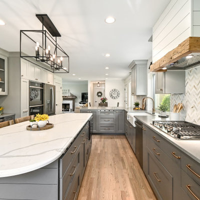 Eat-in kitchen - huge farmhouse l-shaped medium tone wood floor and brown floor eat-in kitchen idea in Milwaukee with a farmhouse sink, shaker cabinets, gray cabinets, quartz countertops, white backsplash, marble backsplash, stainless steel appliances, an island and gray countertops