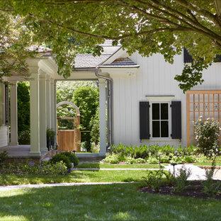 На фото: большой, двухэтажный, деревянный, бежевый частный загородный дом в стиле кантри с крышей из гибкой черепицы, коричневой крышей и отделкой дранкой