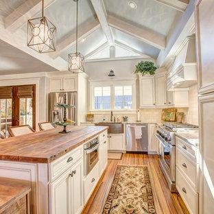 Exempel på ett mellanstort klassiskt kök, med en rustik diskho, släta luckor, vita skåp, träbänkskiva, beige stänkskydd, rostfria vitvaror, bambugolv och stänkskydd i travertin