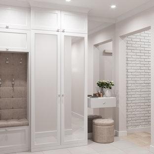На фото: узкая прихожая среднего размера в стиле неоклассика (современная классика) с бежевыми стенами, гранитным полом, одностворчатой входной дверью, входной дверью из светлого дерева, бежевым полом и обоями на стенах