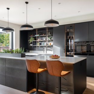 Design ideas for a large contemporary kitchen/diner in Gloucestershire with a built-in sink, flat-panel cabinets, black cabinets, composite countertops, white splashback, black appliances, an island and white worktops.