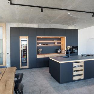 シュトゥットガルトの広いコンテンポラリースタイルのおしゃれなキッチン (ドロップインシンク、フラットパネル扉のキャビネット、黒いキャビネット、御影石カウンター、黒いキッチンパネル、黒い調理設備、黒いキッチンカウンター) の写真
