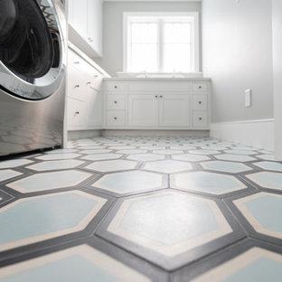 Idéer för en stor eklektisk vita l-formad tvättstuga enbart för tvätt, med en rustik diskho, skåp i shakerstil, vita skåp, bänkskiva i kvarts, vitt stänkskydd, stänkskydd i tegel, vita väggar, betonggolv, en tvättpelare och blått golv