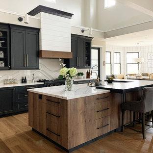 サンタバーバラの広いカントリー風おしゃれなキッチン (エプロンフロントシンク、クオーツストーンカウンター、クオーツストーンのキッチンパネル、黒い調理設備、淡色無垢フローリング、表し梁) の写真