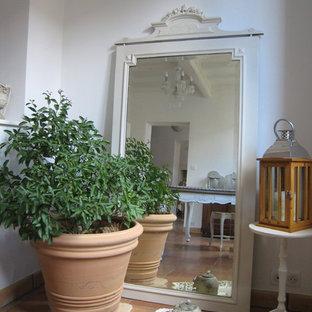 Idee per un soggiorno country di medie dimensioni con pareti bianche, pavimento in terracotta, camino classico e cornice del camino in legno