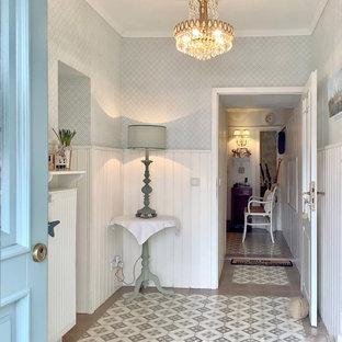 Modelo de entrada panelado, campestre, de tamaño medio, con paredes blancas, suelo de baldosas de porcelana, puerta simple, suelo multicolor, papel pintado y panelado