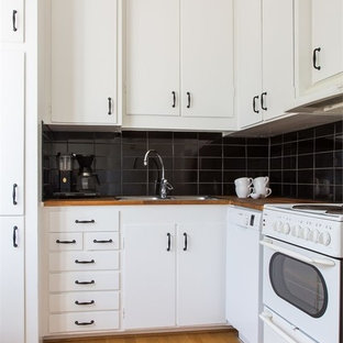 Small modern eat-in kitchen ideas - Inspiration for a small modern medium tone wood floor and multicolored floor eat-in kitchen remodel in Other with a double-bowl sink, flat-panel cabinets, white cabinets, wood countertops, black backsplash, porcelain backsplash, white appliances and no island