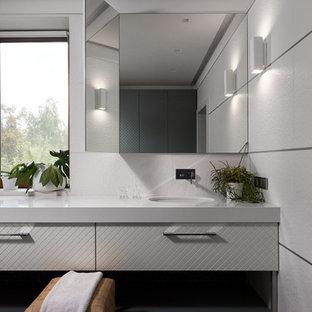 Выдающиеся фото от архитекторов и дизайнеров интерьера: ванная комната в современном стиле с плоскими фасадами, белыми фасадами, белой плиткой, врезной раковиной, коричневым полом и белой столешницей