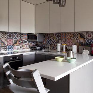 Неиссякаемый источник вдохновения для домашнего уюта: п-образная кухня в современном стиле с врезной раковиной, белыми фасадами, столешницей из акрилового камня, разноцветным фартуком, фартуком из керамической плитки, техникой из нержавеющей стали, полом из ламината, бежевым полом, белой столешницей, плоскими фасадами и полуостровом