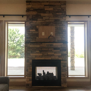Two-Sided Fireplace with Stone Surround and TV mounted above