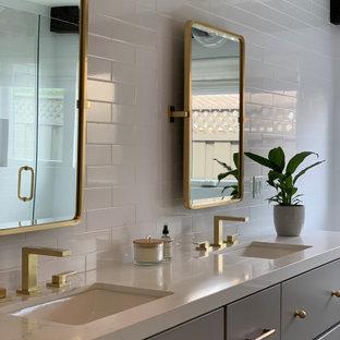 Inspiration för stora lantliga vitt en-suite badrum, med släta luckor, grå skåp, ett platsbyggt badkar, en dusch i en alkov, en toalettstol med hel cisternkåpa, vit kakel, keramikplattor, vita väggar, marmorgolv, ett undermonterad handfat, bänkskiva i kvarts, svart golv och dusch med gångjärnsdörr