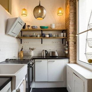 Offene, Kleine Nordische Küche in L-Form mit Landhausspüle, Küchengeräten aus Edelstahl, Zementfliesen und grauem Boden in Berlin