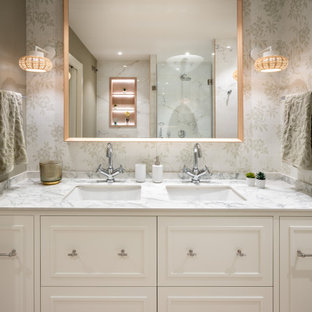Photo of a mid-sized transitional master bathroom in Other with raised-panel cabinets, white cabinets, a curbless shower, white tile, green walls, laminate floors, an undermount sink, granite benchtops, brown floor, white benchtops, a double vanity, a built-in vanity and wallpaper.