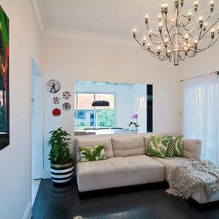 Imagen de sala de estar tropical, pequeña, sin chimenea y televisor, con paredes blancas, suelo de madera oscura y suelo negro