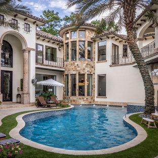 Immagine di un'ampia piscina naturale mediterranea personalizzata in cortile con una vasca idromassaggio