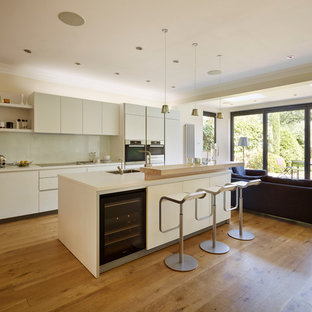 Photo of a contemporary galley open plan kitchen in Cheshire with a submerged sink, flat-panel cabinets, white cabinets, white splashback, glass sheet splashback, medium hardwood flooring, an island and stainless steel appliances.