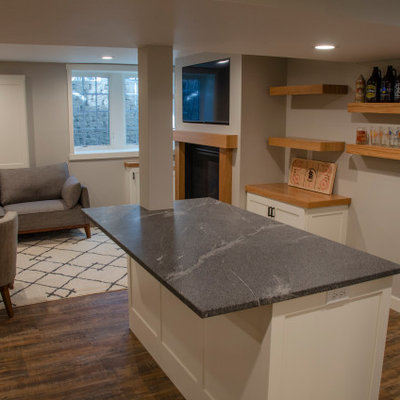 Mid-sized elegant vinyl floor and brown floor basement photo in Minneapolis with a bar, a standard fireplace and a wood fireplace surround