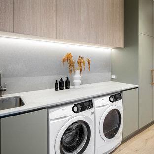 Foto di una lavanderia multiuso contemporanea di medie dimensioni con lavello sottopiano, ante verdi, top in marmo, paraspruzzi grigio, paraspruzzi in lastra di pietra, pareti bianche, parquet chiaro e lavatrice e asciugatrice affiancate