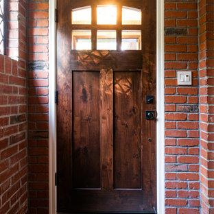 Свежая идея для дизайна: входная дверь среднего размера в классическом стиле с красными стенами, полом из керамической плитки, одностворчатой входной дверью, входной дверью из темного дерева, серым полом и кирпичными стенами - отличное фото интерьера