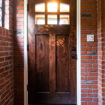 Dark Wood Door with Divided Glass Windows in Red Brick Entryway