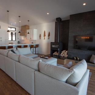 Esempio di un grande soggiorno minimalista aperto con pareti bianche, pavimento in laminato, stufa a legna, cornice del camino piastrellata, TV a parete e pavimento marrone