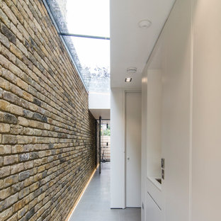 Пример оригинального дизайна: большой коридор в современном стиле с полом из известняка, серым полом, кессонным потолком и кирпичными стенами