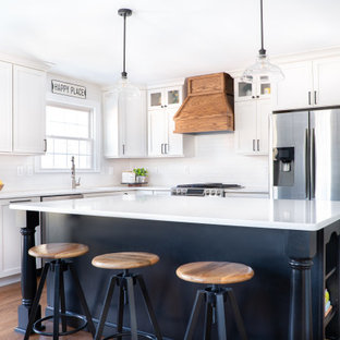 Mid-sized transitional l-shaped medium tone wood floor and brown floor eat-in kitchen photo in Baltimore with an undermount sink, shaker cabinets, white cabinets, quartz countertops, white backsplash, porcelain backsplash, stainless steel appliances, an island and white countertops