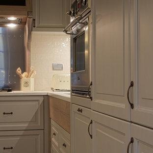 Große Shabby-Chic-Style Wohnküche in U-Form mit Doppelwaschbecken, profilierten Schrankfronten, türkisfarbenen Schränken, Mineralwerkstoff-Arbeitsplatte, Küchenrückwand in Weiß, Rückwand aus Keramikfliesen, Küchengeräten aus Edelstahl, Zementfliesen, Halbinsel, türkisem Boden und weißer Arbeitsplatte in Rom